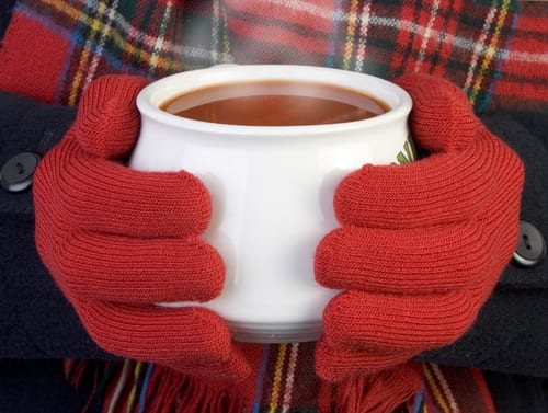 Person wearing mittens holding a mug of coffee