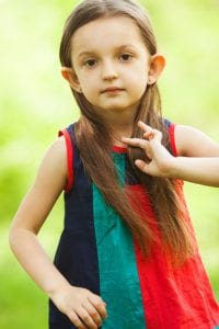 Portrait of funny, sweet, little, charismatic girl touching her long hair.